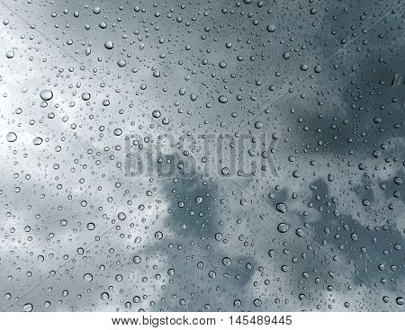Drops of rain on glass , rain drops on clear window / rain drops with clouds / water drops on glass after rain background / water drops / Small water drops on the glass