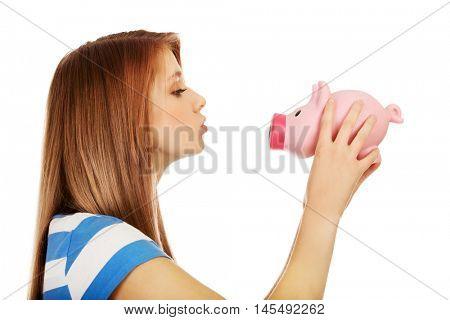 Happy teenage woman kissing a piggybank
