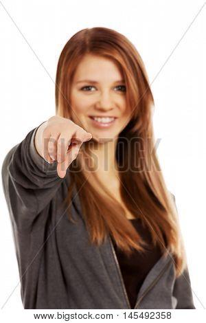 Beautiful teenage woman pointing at camera