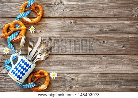 Bavarian pretzels with silverware and beer stein on wooden board. Background for Oktoberfest