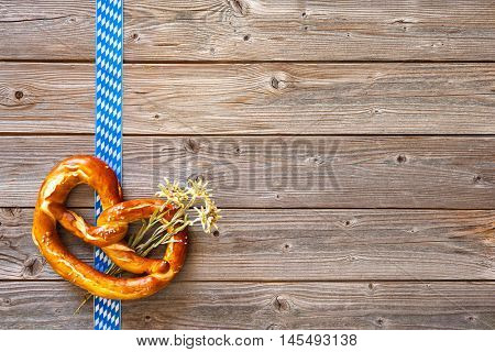 Bavarian pretzel with ribbon and edelweiss on wooden board. Background for Oktoberfest