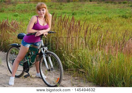 sexy woman on bicycle on nature outdoors