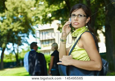 Busy caucasian businesswoman making a mobile phone call on the street, outdoor. Wearing glasses, shoulder bag, looking back.