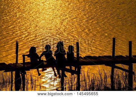 Girls sitting wooden on the old bridge to see sunset in rural of Thailand