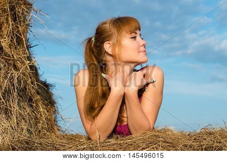 beautiful woman in haystack outdoors on nature