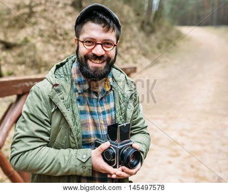 Portrait of a nice smiling male photographer with film cameras on a wooden bridge in a picturesque forest life style hipster trips