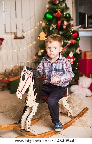 Small Boy Riding Wooden Rocking Horse In Front Of Christmas Tree