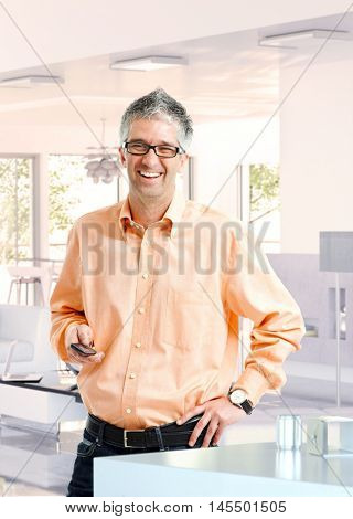 Laughing casual caucasian mature businessman at home with phone in hand, smiling, standing, hand on hip, wearing glasses, looking at camera.