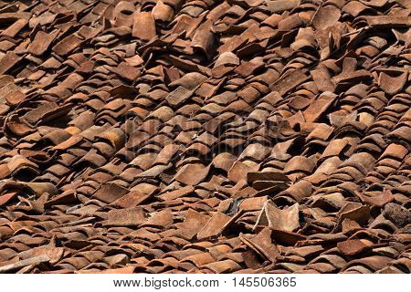 Background ornament terracotta red ancient tiles. Destructed roof, India, Karnataka