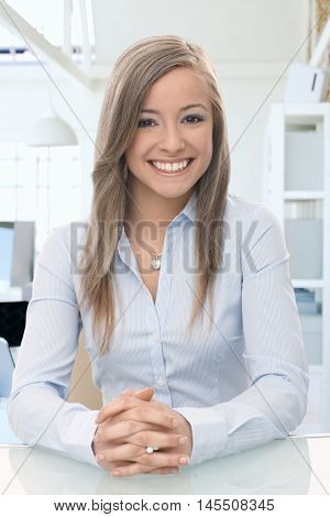 Happy casual woman sitting at office desk, looking at camera, smiling.