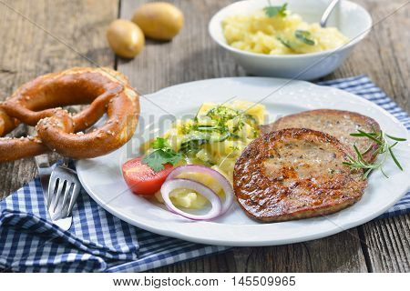 Bavarian food: Fried slices of sausage with pieces of pig spleen (so called 'Milzwurst') served with potato salad and a fresh pretzel
