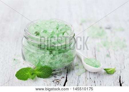 Sea salt bath scented mint for spa and aromatherapy on white wooden background, rustic style.