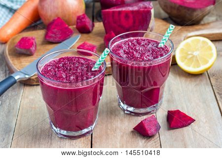 Healthy detox beetroot carrot apple and lemon juice smoothie in glass on wooden table horizontal