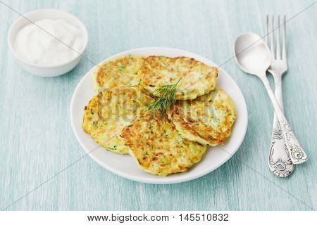 Zucchini cabbage pancakes or vegetable fritters with sour cream on wooden kitchen table.