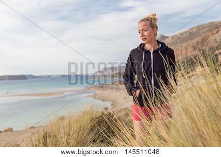 Relaxed woman in dark hoodie walking on serene Balos beach, Greece, enjoying beautiful nature and nice views.
