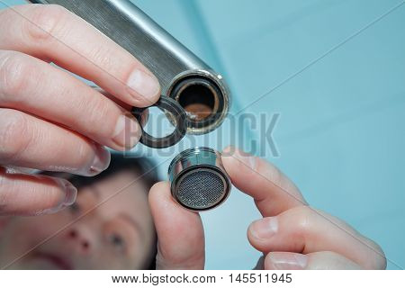Woman plumber installing faucet aerator close-up of hand handyman repairing a tap in the bathroom.