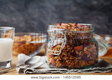 Homemade granola in jar on white table. Healthy breakfast of oatmeal, muesli, nuts, seeds and dried fruit.