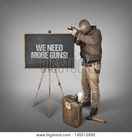 We need more guns text on blackboard with man holding machine gun
