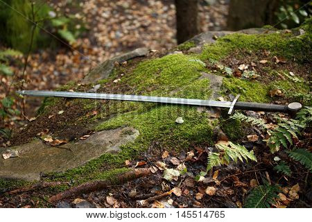 cold steel arms. Two-handed sword is lying on the moss-covered stone.