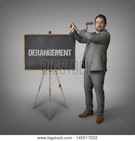 Derangement text on blackboard with businessman drilling his head