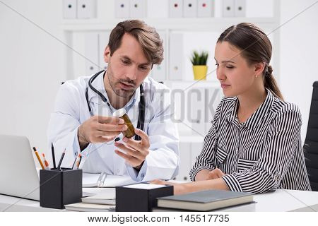 Doctor is showing patient pills he has just prescribed and explaining how to take them. Concept of good doctor and modern clinic