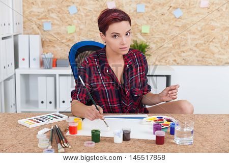 Woman painter at her workplace is getting ready to give art class to housewives. Concept of education in art and sculpture