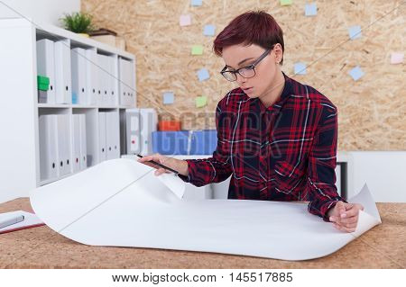 Woman architect working with blueprints in her office. Concept of engineering and development