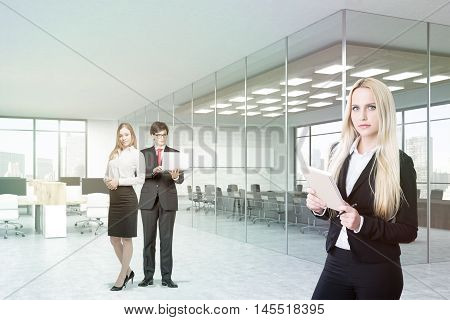 Businesspeople portrait in office. Man and woman stand in background holding laptop. Blond woman in foreground with notepad. Conference room with concrete walls. 3d rendering.