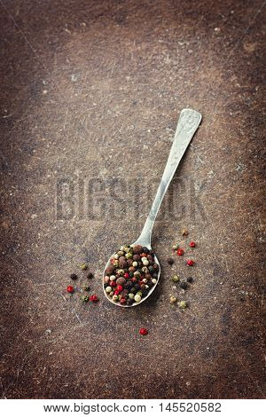 Peppercorn in a spoon on vintage shabby surface. Top view. Copy space for text.