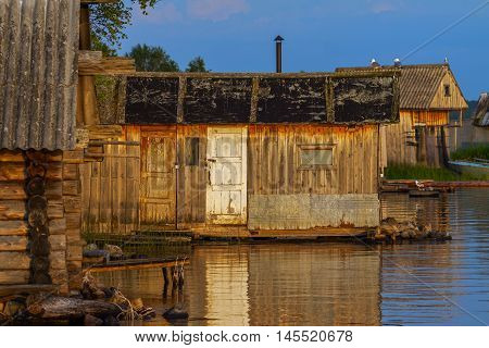 Old bathhouses on lake in sundown light with selective focus