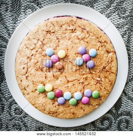 Tasty cake with colorful smarties in funny face shape. Festive sweet food. Positive emotions.
