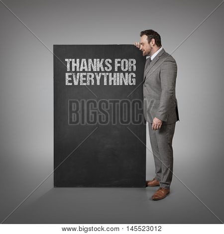 Thanks for everything text on blackboard with businessman standing side