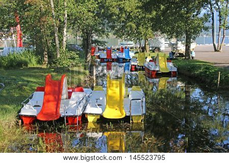 Colourful Paddle boats moored in a stream