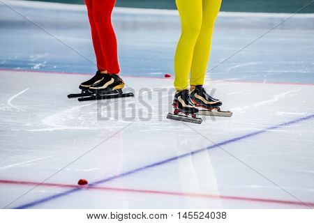 legs of two girls speed skaters at starting line during competition in speed skating