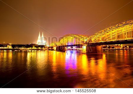 Cologne in Germany at night with the river Rhein and the famous cathedral in the background.