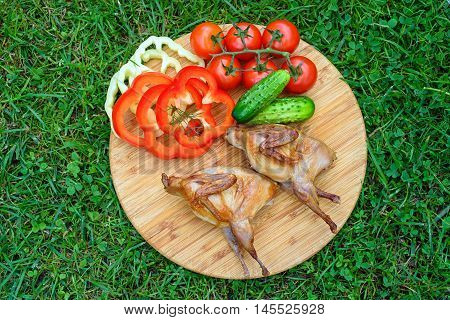 Delicious fried quail with fresh juicy vegetables on the wooden round board on green grass. Prepared tomato, cucumber, sweet pepper, partridge, quail.