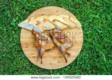 Delicious fried quail with fresh slice of bread on the wooden round board on green grass.