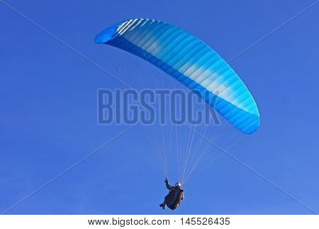 paraglider flying under his wing in a blue sky