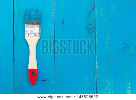 Large paint brush with wooden handle and blue wooden backgraund
