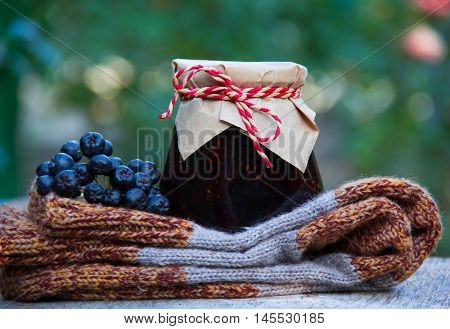 Grandma's gift. Homemade jam, knitted woolen socks and black chokeberry. Autumn concept.