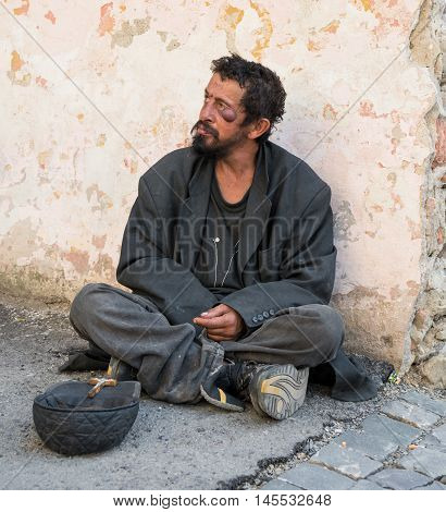 Homeless dirty man on the street of the city