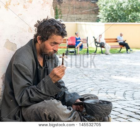 Homeless dirty man with cross on the street of the city