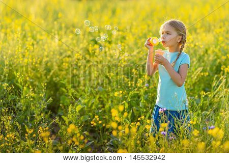Bubbles are fun for everyone. Cute little girl with pigtails blowing soap bubbles, standing in field around grass and wildflowers