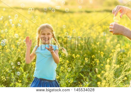 Everyone loving bubbles. Shot of cute girl trying to touch bubbles floating in air around her outdoors and smiling