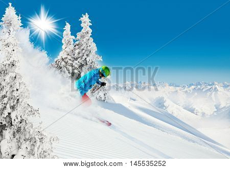 Skier on piste running downhill in beautiful Alpine landscape. Blue sky on background. Free space for text