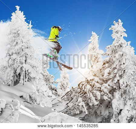 Skier at jump in Alpine mountains in beautiful sunny day. Copyspace for text