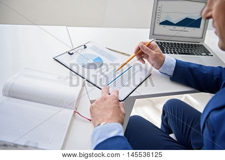 Getting down to business. Top view of mature businessman working with document and graph at his office