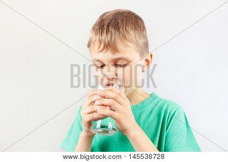 Little blonde boy drinking a fresh mineral water