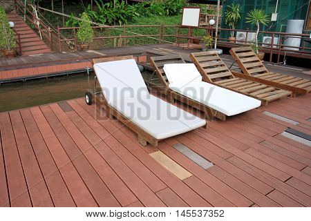 a sundeck on wooden floor of floating raft on River Kwai Noi Resort for relaxing holiday in Kanchanaburi Province at Thailand.