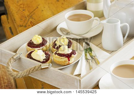Tea with home made scones topped with Cornish clotted cream and strawberry jam on a wooden tray
